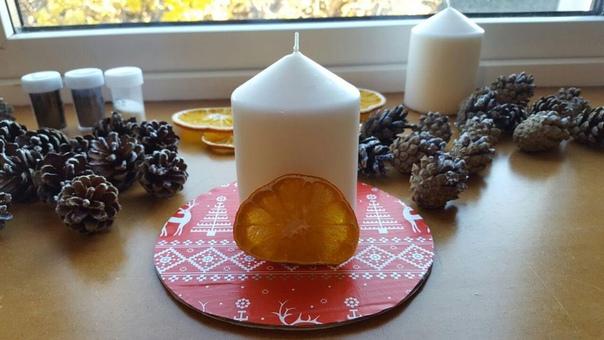 Дeкорируем подсвечник к Новому году для работы понадобится: - свеча; - плотный картон; - шишки; - засушенные дольки апельсина; - елочные веточки; - блестки или крупная соль; - новогодняя